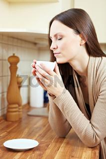 Frau riecht an Tasse Kaffee