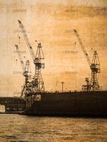 Three cranes in the port of Hamburg in vintage look