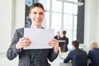 Junger Geschäftsmann hält leeres Schild im Büro