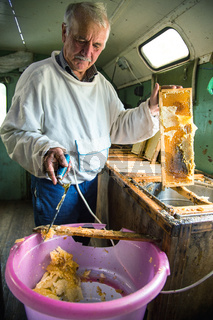 The beekeeper separates the wax from the honeycomb frame.