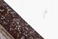 Frosted snowflakes and ice on natural brown wood. Copyspace area for winter design and construction based themes and concepts.