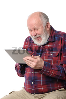 Senior man laughing with something at screen of tablet computer, isolated on white