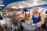 Young people exercising on bikes in fitness gym
