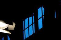 Abstract picture of a window frame with a blue sky and a cropped spotlight in the front.