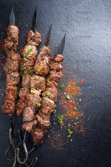 Traditional Russian shashlik on a barbecue skewer as top view on slate slab