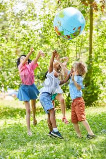 Multikulturelle Gruppe Kinder spielt mit Weltkugel