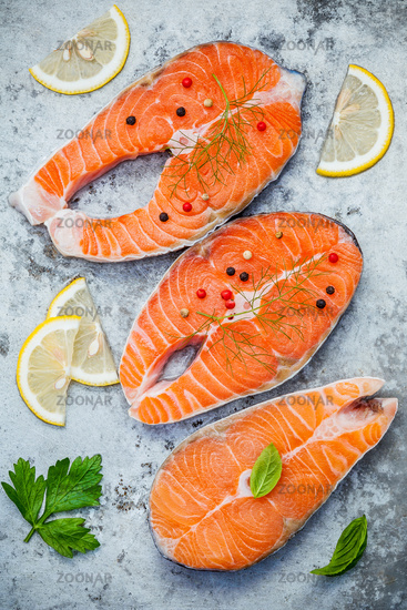 Fresh salmon fillet sliced flat lay on shabby metal background. Raw salmon fillet and ingredients parsley ,sweet basil leaves ,fennel ,pepper corn and lemon for cooking.
