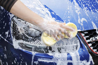 Washing the headlight of a car with a sponge