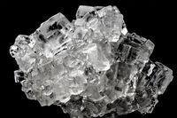 Cubic salt crystal aggregate against black background