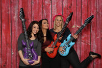 3 girls with plastic guitars in front of a photo box