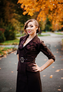 Portrait of smart girl with old-fashioned hairstyle outdoor in brown coat on autumn.