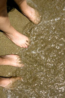 Feet of Two Girls in Sand at Beach with Water
