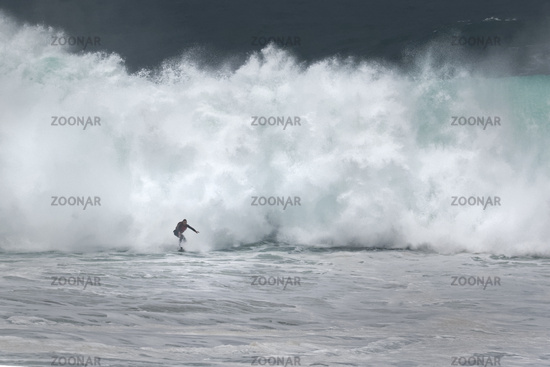 Surfer on surf board riding wave, Nazare, Portugal, Europe