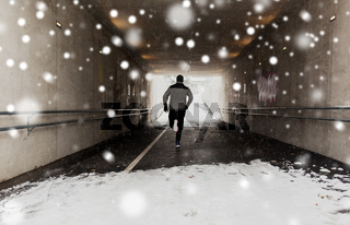 man running along subway tunnel in winter