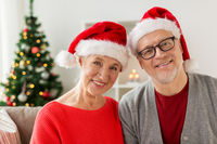 happy senior couple in santa hats at christmas