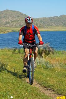 Bike tourist on green field beside lake