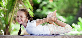 Child doing exercise on platform outdoors. Healthy lifestyle. Yoga girl