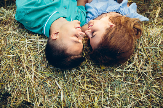 man and woman lie on hay