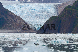 Man in Boat in Front of Sawyer Glacier at Tracy Arms Fjords in Alaska United States.