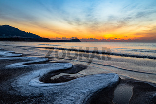 24th Jan 2018, Qingdao, Shandong. Sunrise on Shilaoren Beach, in a morning so cold that the water from the sea is turned into ice