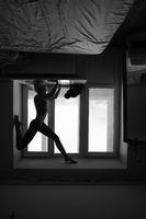 woman doing yoga asana on window sill