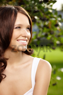 Portrait of fine young woman with curly hair against a summer garden