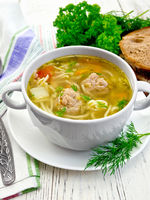 Soup with meatballs and noodles in white bowl on board
