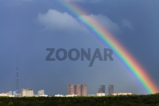 rainbow in dark blue sky over city with TV tower