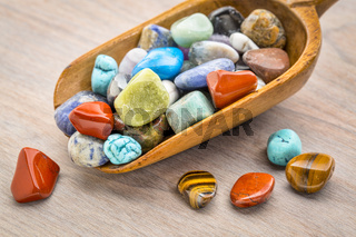 polished, colorful gemstone in rustic wooden scoop