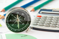 Business graphs and finances with a compass