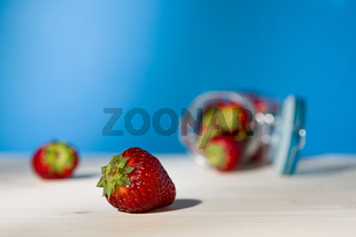 Close up of a strawberry and a glass jar full of strawberries lying down on a table