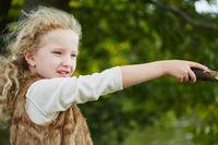Mädchen spielt mit einem Stück Holz