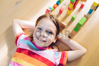 Amused little girl lying on her back on the floor - colorful wooden blocks arranged around her