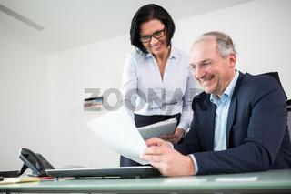 Geschäftsführer und Kollegin mit Akte