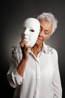mature woman revaling sad face behind mask