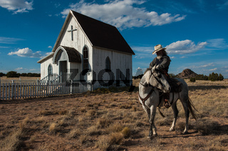 Man on a horse rides past a country church in the country.