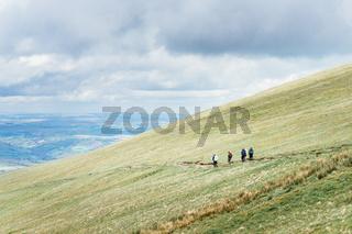 People in distance hiking on the hillside near to Pan Y Fan in Brecon Beacons, Wales