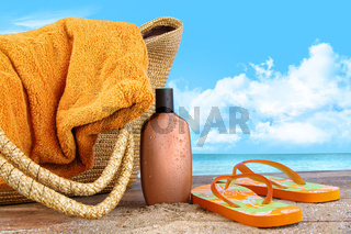 Suntan lotion, with towel at the beach
