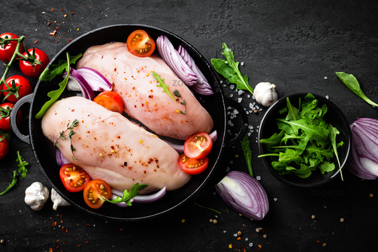 Fresh raw chicken meat, fillet marinated with spices, onion and tomatoes on black background. Top view