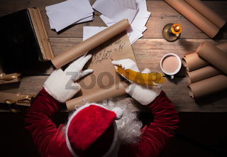 Santa Claus sitting at the table in his room and writing Christmas letter or wish list