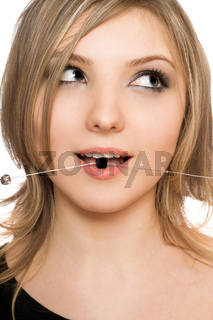Close-up portrait of attractive girl with a bead in her mouth