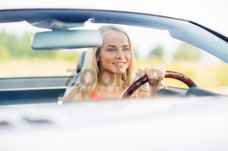 happy young woman driving convertible car