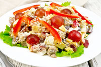 Salad of meat and cheese with grapes on green lettuce
