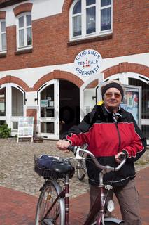 Aktive Gäste - Urlauberin mit Fahrrad vor Gardinger Tourist Info; Garding