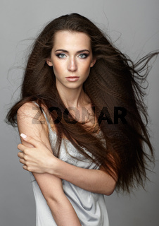 Beauty portrait of young woman. Brunette girl with long disheveled flying hair and day female makeup on gray background