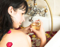 Young woman with a drink in rose petal bath