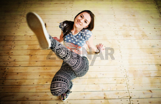 Street dancer girl wearing casual clothes on footless sitting background wooden parquet indoor.