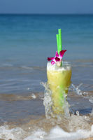 Glass Of Juice Cocktail With Two Straws Washed By Waves On The Beach