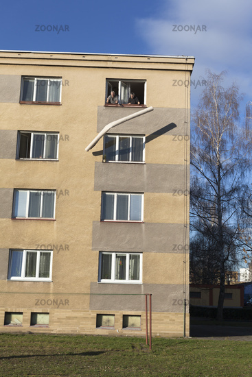 Seniors throwing rolled carpet out of a window of a building