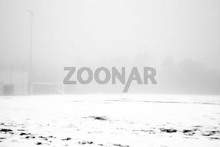 Fußballplatz im Schnee und Nebel